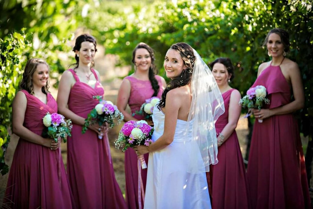 A bride and her bridesmaids in fuschia dresses all holding flowers