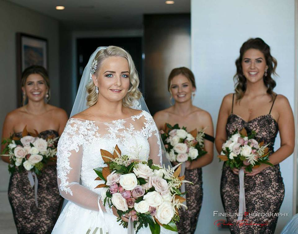 A bride with her bridesmaids holding flowers.