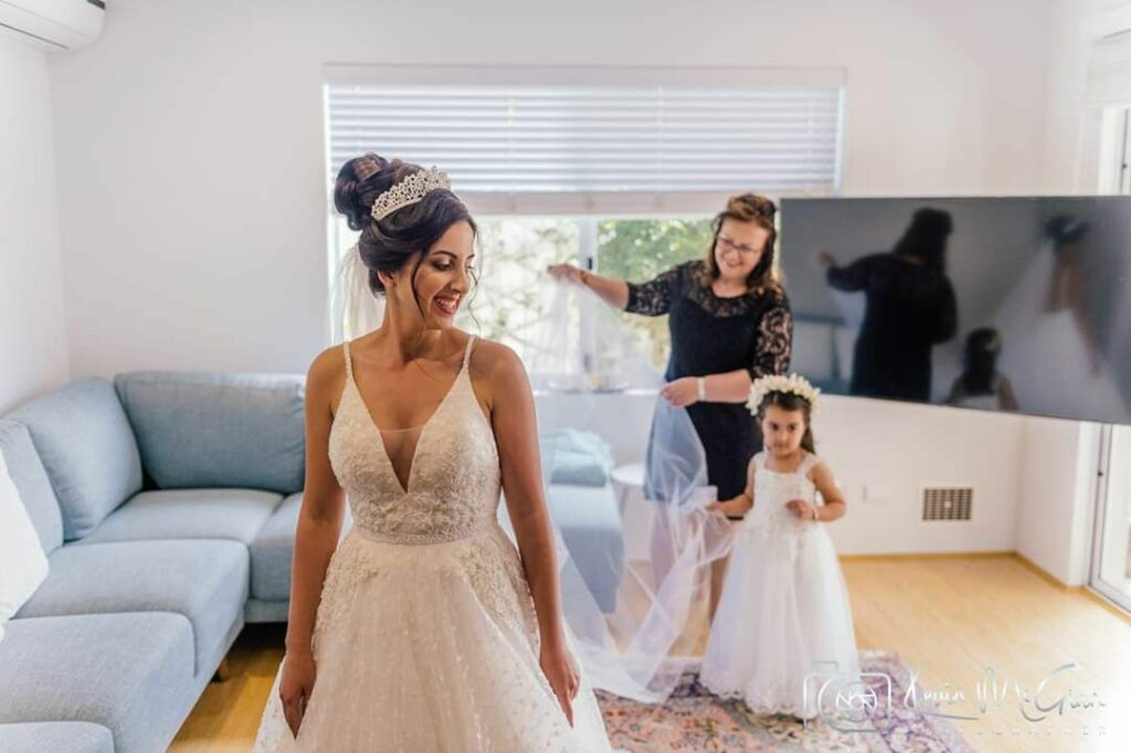 A bride and flower girl in their lounge room.