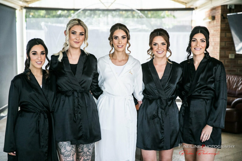 A bride with styled hair with her 4 bridesmaids in black dresses